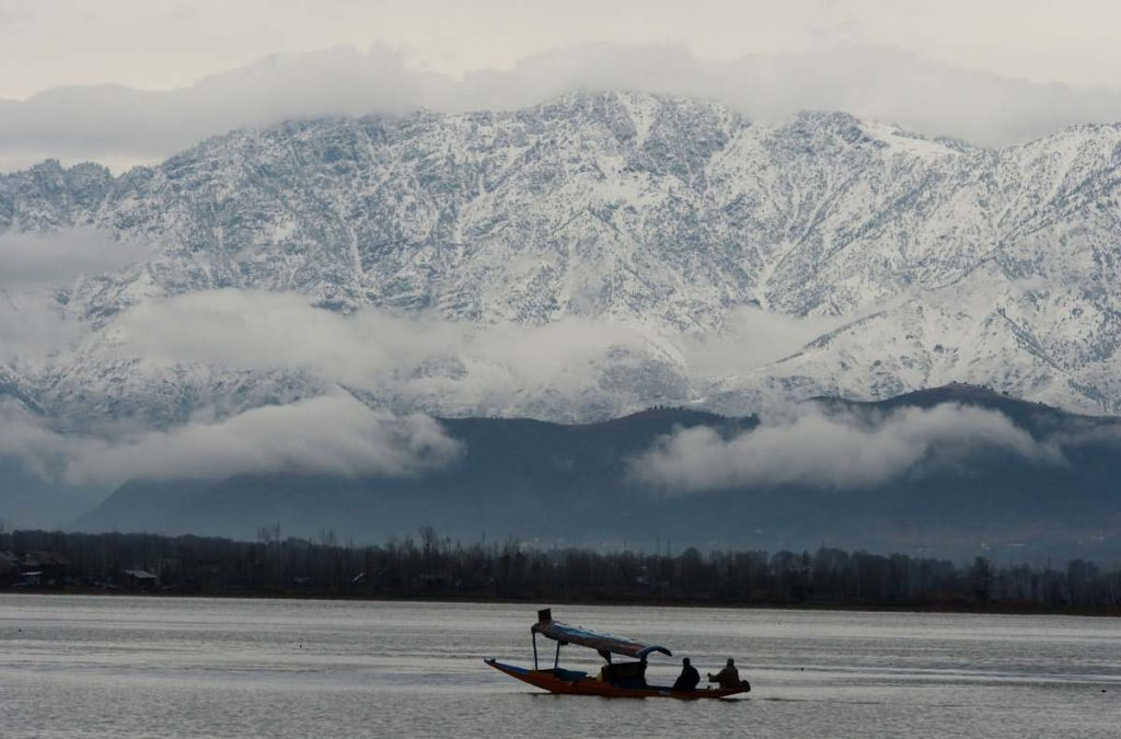 boating in a lake near snow filled mountains at kashmir