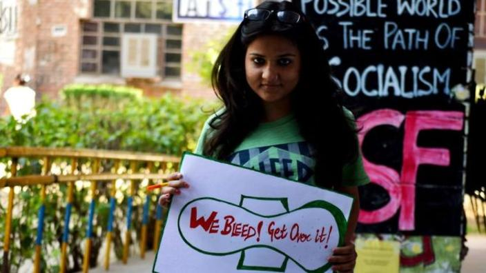 we bleed, get over it placard held by a girl