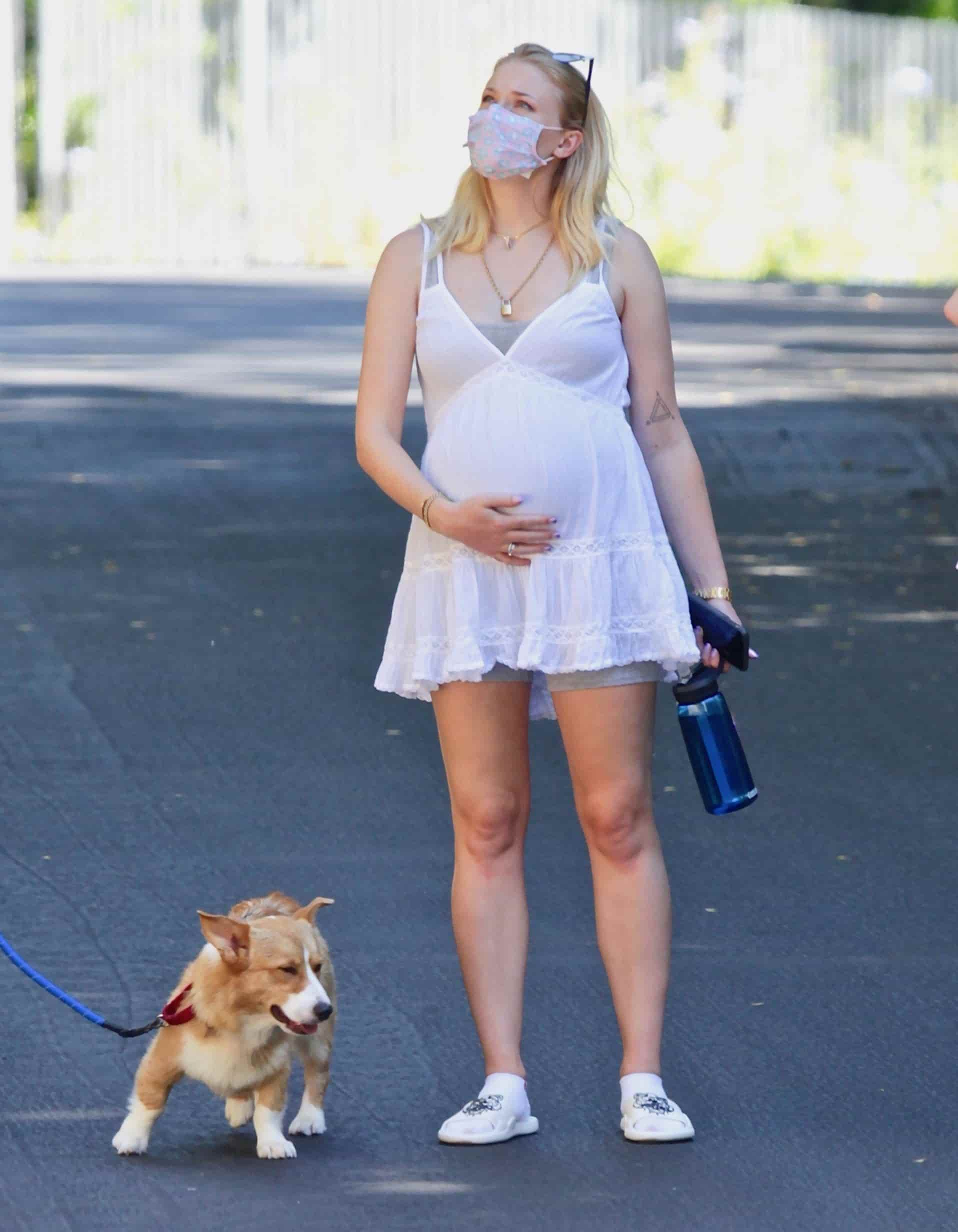 sophie turner wearing white dress and cute little skirt taking a walk with a dog while she was pregnant