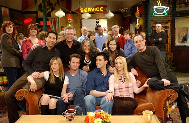 friends cast along with directors sitting on orange couch