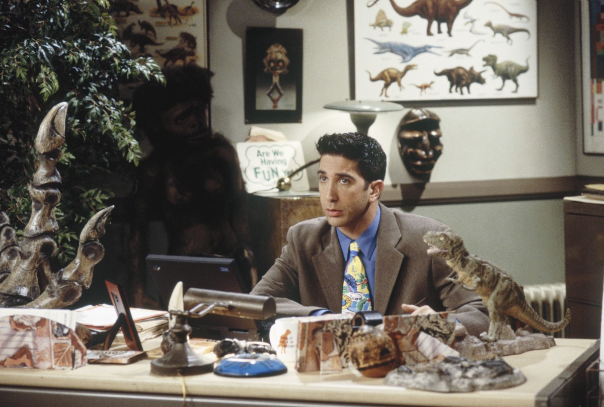 ross geller in his museum playing with his dinosaurs as a nerd